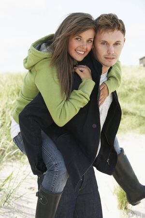 Young Man Giving Woman Piggyback In Dunes With Beach Hut In Distance photo