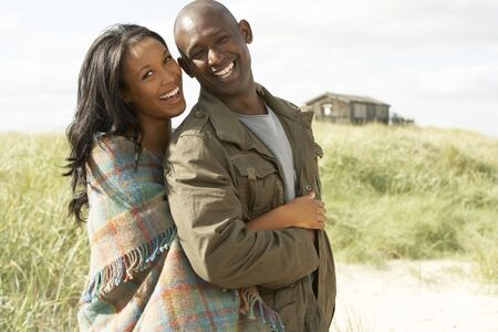 Romantic Young Couple Standing By Dunes With Beach Hut In Distance photo