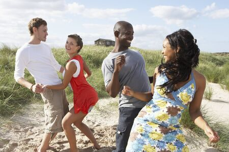 Group Of Young People Having Fun Dancing On Beach Together photo
