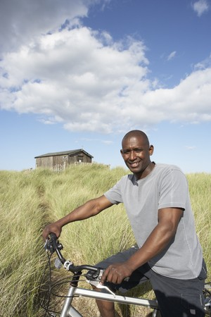Young Man Riding Mountain Bike By Dunes With Old Beach Hut In Distance photo