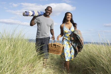 and the horizontal man: Young Couple Carrying Picnic Basket And Windbreak Walking Through Dunes Stock Photo