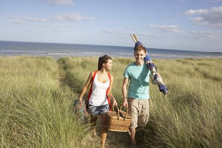 man carrying woman: Young Couple Carrying Picnic Basket And Windbreak Walking Through Dunes Stock Photo