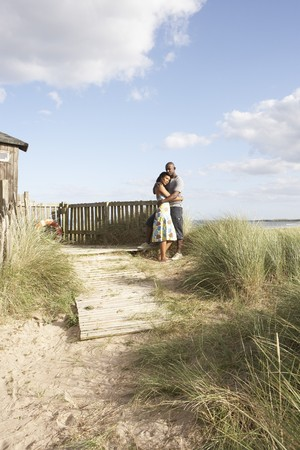 Romantic Young Couple Standing By Wooden Fence Of Beach Hut Amongst Dunes photo
