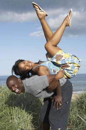 Couple de jeunes �nergique amusant dans les dunes par plage