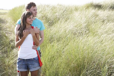 Romantic Young Couple Standing Amongst Dunes photo