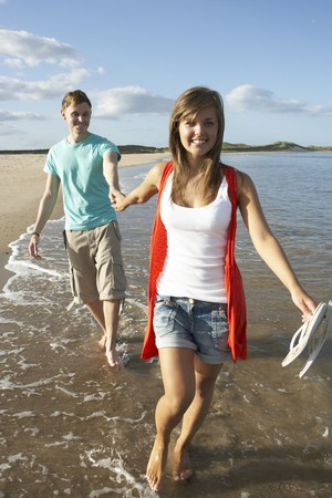 Romantic Young Couple Walking Along Shoreline Of Beach Holding Hands photo