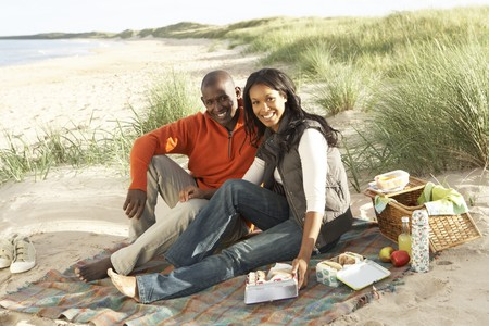 Young Couple Enjoying Picnic On Beach Together photo