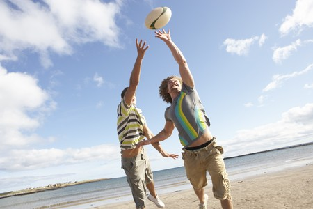 teens playing: Two Teenage Boys Playing Rugby On Beach Together