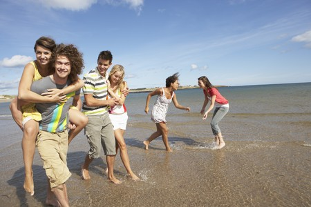 Group Of Young Friends Walking Along Summer Shoreline photo