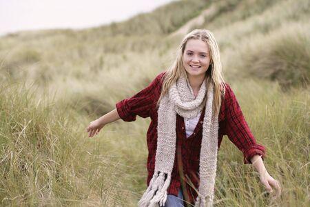 Teenage Girl Walking Through Sand Dunes Wearing Warm Clothing photo