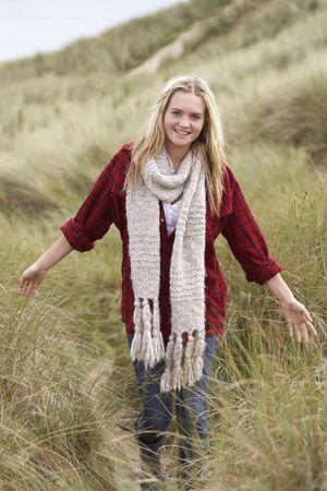 scarf beach: Chica adolescente caminando a trav�s de las dunas wearing ropa caliente