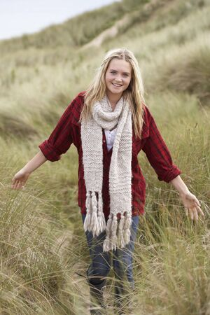 Teenage Girl Walking Through Sand Dunes Wearing Warm Clothing photo