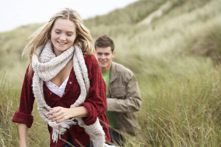Young Couple Walking Through Sand Dunes Wearing Warm Clothing photo