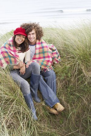 Young Couple Sitting In Sand Dunes Wrapped In Blanket photo