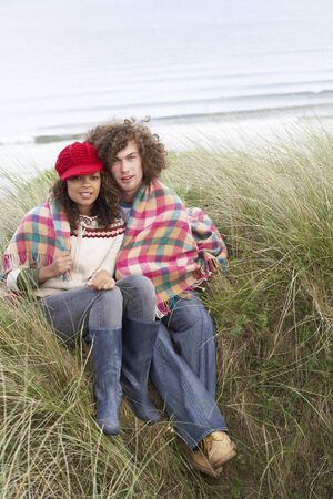 Young Couple Sitting In Sand Dunes Wrapped In Blanket Stock Photo - 7175889
