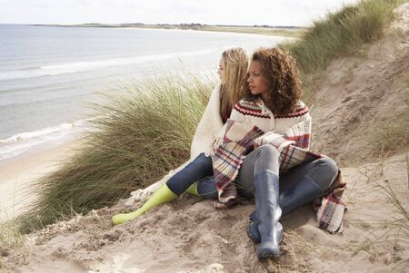 Two Teenage Girls Sitting In Sand Dunes Wrapped In Blanket photo