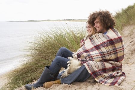 Teenage Couple Sitting In Sand Dunes Wrapped In Blanket photo