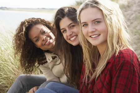 Three Teenage Girls Sitting In Sand Dunes Together photo