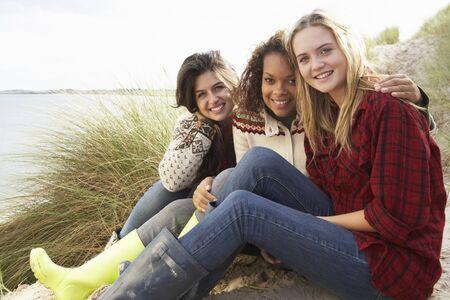 Three Teenage Girls Sitting In Sand Dunes Together photo