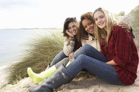 Three Teenage Girls Sitting In Sand Dunes Together Stock Photo - 7175682