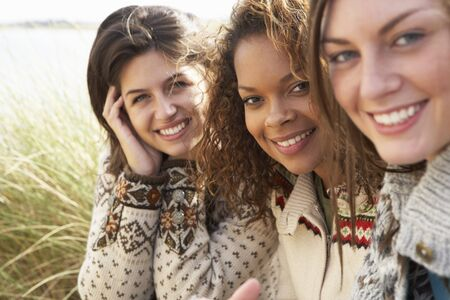 Three Young Girls Sitting In Sand Dunes Together photo