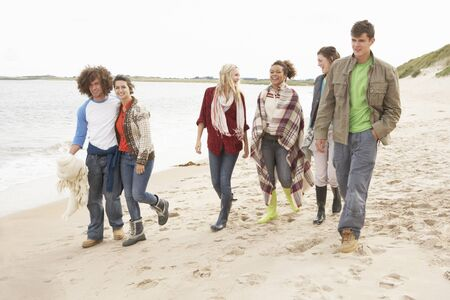 Group Of Young Friends Walking Along Autumn Shoreline photo