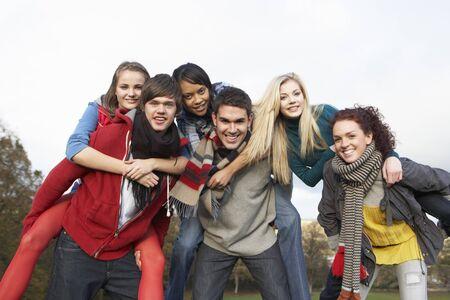 Group Of Teenage Friends Having Piggyback Rides In Autumn Landscape photo