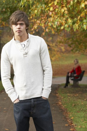 silhouette femme: Teenage Boy Standing In Autumn Park With Female Figure On Bench In Background