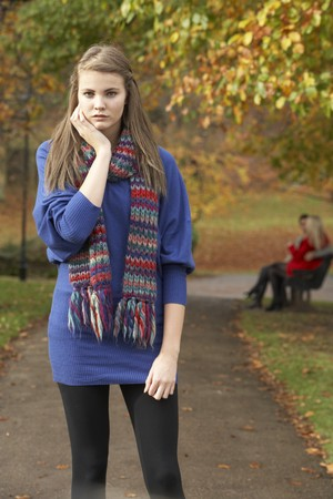 Unhappy Teenage Girl Standing In Autumn Park With Couple On Bench In Background photo