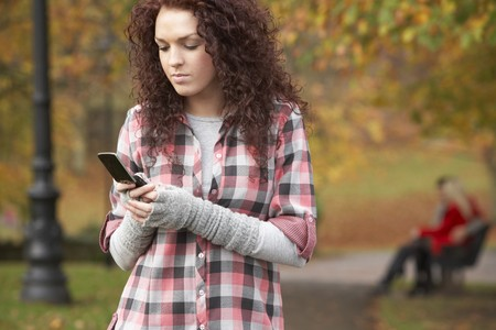 Frustrated Teenage Girl Making Mobile Phone Call In Autumn Landscape photo