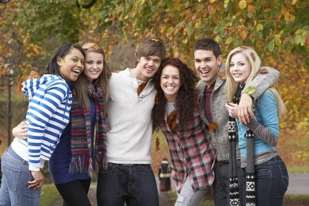 friends having fun: Group Of Six Teenage Friends Having Fun In Autumn Park