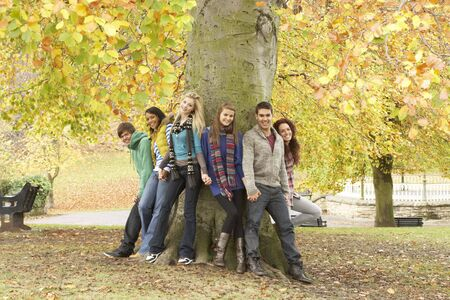 Group Of Six Teenage Friends Leaning Against Tree In Autumn Park photo