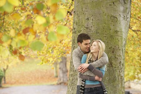 women hugging: Romantic Teenage Couple By Tree In Autumn Park Stock Photo