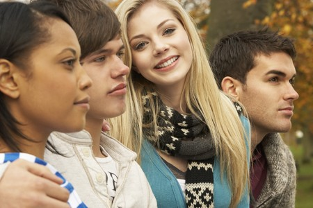 Close Up Of Group Of Four Teenage Friends In Autumn Woodland photo