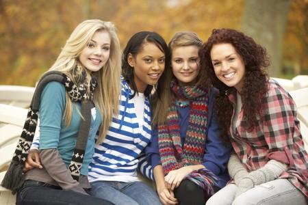 chicas adolescentes: Grupo de cuatro chicas adolescentes, sentado en el Banco en el Parque de oto�o