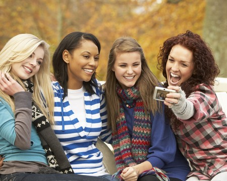 Group Of Four Teenage Girls Taking Picture With Camera Sitting On Bench In Autumn Park photo