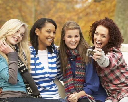 group picture: Grupo de cuatro ni�as adolescentes toma de fotograf�a con la c�mara, sentado en el Banco en el Parque de oto�o  Foto de archivo