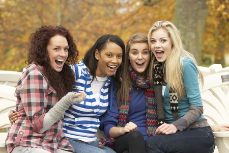 Group Of Four Teenage Girls Sitting On Bench In Autumn Park Stock Photo - 7175730