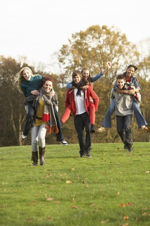 piggyback: Group Of Teenage Friends Having Piggyback Rides In Autumn Landscape