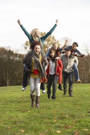 parejas caminando: Grupo de amigos adolescentes despu�s de haber Piggyback cabalga en paisaje de oto�o