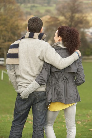 Back View Of Romantic Teenage Couple In Autumn Landscape photo