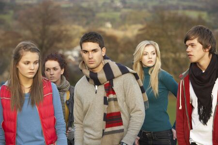 Teenage Boy Surrounded By Friends In Outdoor Autumn Landscape photo