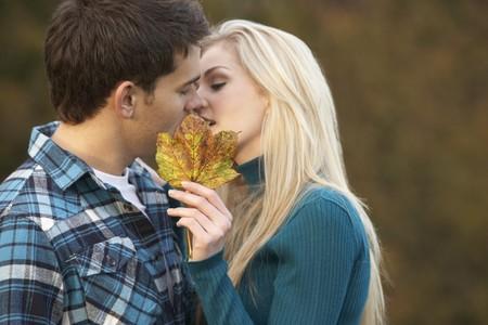 Romantic Teenage Couple Kissing Behind Autumn Leaf photo