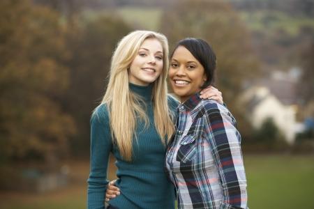 Two Female Teenage Friends On Walk In Autumn Landscape photo