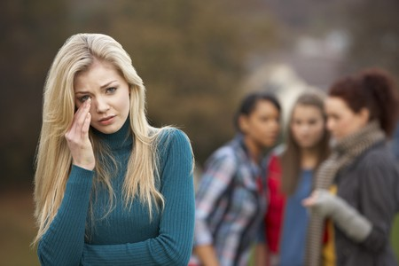bully: Upset Teenage Girl With Friends Gossiping In Background