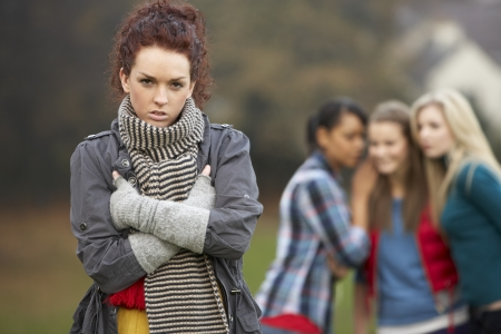 rumours: Upset Teenage Girl With Friends Gossiping In Background