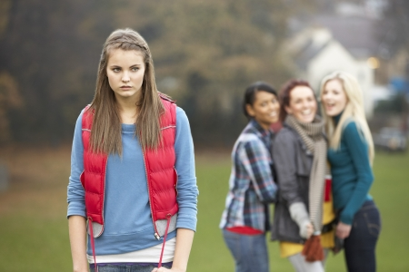 mixed race teen: Upset Teenage Girl With Friends Gossiping In Background