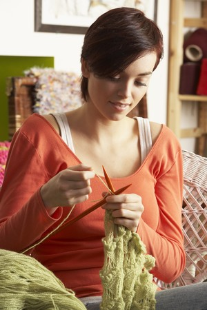 knitting needles: Young Woman Sitting In Chair Knitting