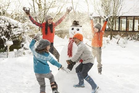 bonhomme de neige: M�re et enfants b�timent Bonhomme de neige dans le jardin