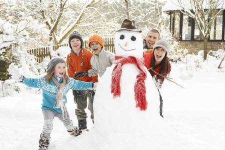 women having fun: Family Building Snowman In Garden Stock Photo
